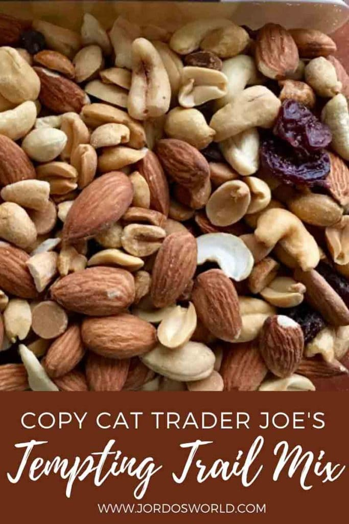 This is a pin for the Copy Cat Trader Joe's Tempting Trail Mix recipe. There is a picture of trail mix with nuts, dried fruit and chocolate. The title of the post, Tempting Trail Mix, at the bottom of the post.