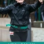 """This is a pin for my first marathon race. It has a girl wearing black shorts, a black coat, a race number and a white hat while she is running in the rain. The title of the post, """"How I Ran My First Marathon"""" across the top of the picture."""