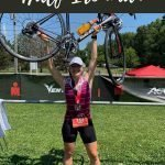 """This is a pin for my first half ironman race. It has a girl holding a bike over her head wearing a race number, with the title of the post """"First Triathlon"""" across the picture."""