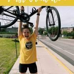 """This is a pin for my first half triathlon race. It has a girl in black shorts and a yellow shirt holding a bike over her heard. The title of the post, """"How I Trained for my First Triathlon"""" is across the picture."""