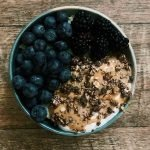 """This is a pin for protein oatmeal. There is a bowl of oatmeal topped with fruit, nut butter, and granola. The title of the recipe, """"Healthy Protein Oatmeal"""" is across the top of the image."""