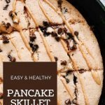 This is a pin for the easy pancake skillet recipe. There is a cast-iron skillet with a big protein pancaked topped with nut butter and mini chocolate chips. The title of the recipe is in a box on the left-hand corner of the pin.