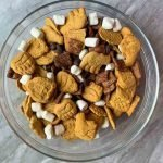 This is a pin for a S'mores Trail Mix recipe. There is a small container of trail mix with the title of the recipe across the top.