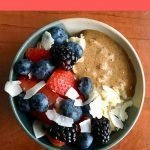 This is a pin for protein oatmeal. There is a bowl of oatmeal topped with berries, nut butter, and coconut flakes. The title of the recipe is across the top of the picture.