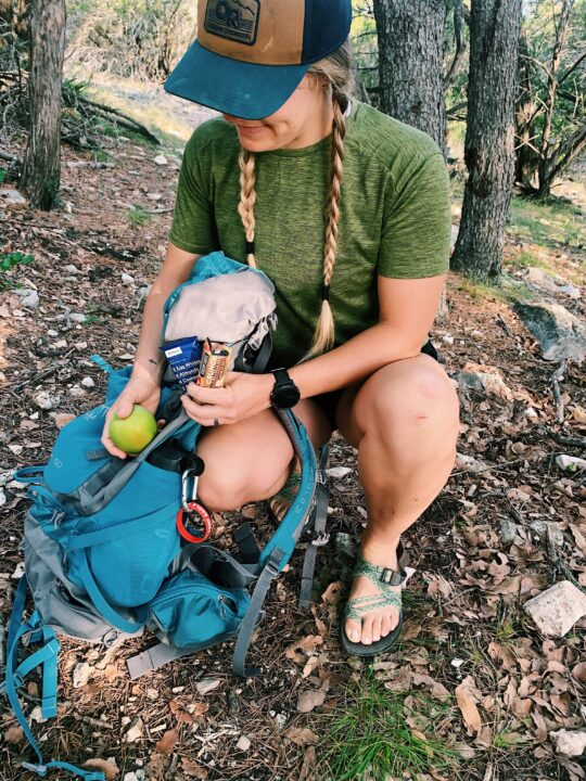 This is a picture of a girl with a green shirt and blue backpack leaning over a backpack getting out hiking snacks. There is an apple and protein bars in her hand.