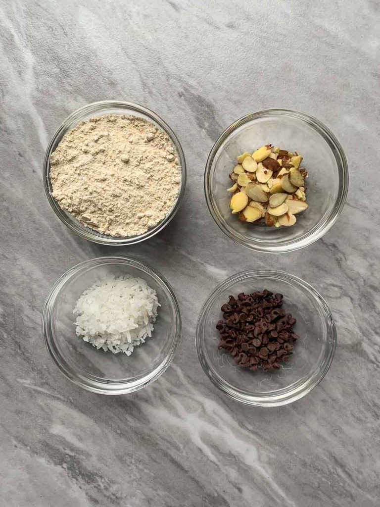 This is a picture of the ingredients for the almond joy pancakes. There are four small bowls, one with pancake mix, one with almonds, one with coconut, and one with chocolate chips.