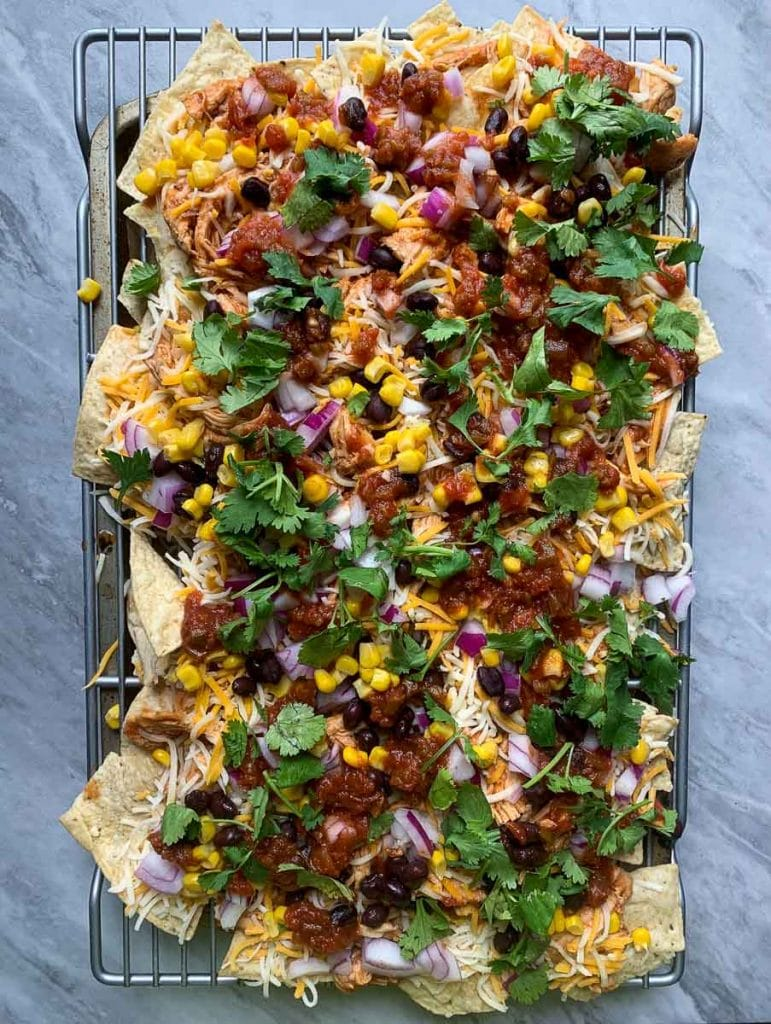 This is a picture of sheet pan BBQ chicken nachos. On the nachos is shredded bbq chicken, black beans, corn, cilantro, red onions, and cheese.