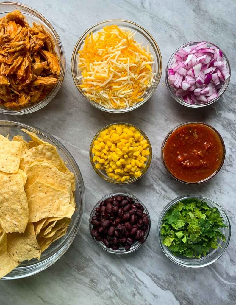 This is a picture of all of the ingredients for sheet pan bbq chicken nachos. Each bowl has an ingredient. There is a bowl of bbq shredded chicken, tortilla chips, cheese, corn, black beans, red onions, salsa, and cilantro.