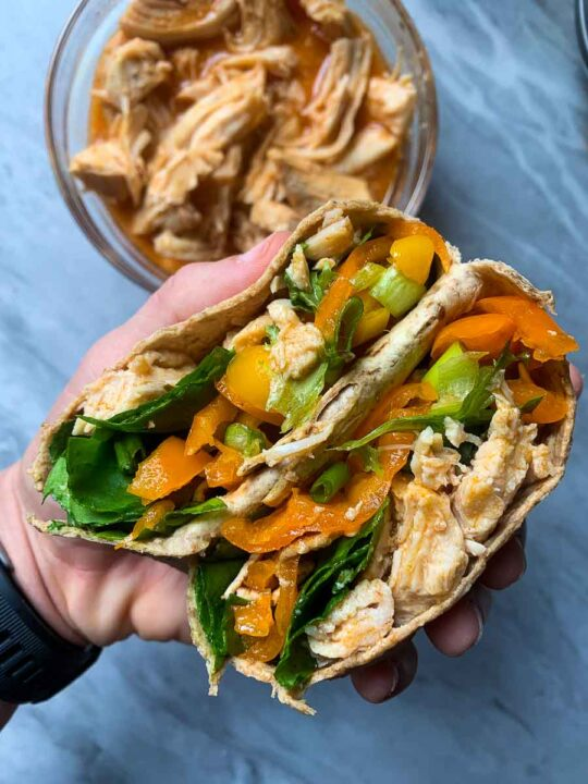 This is the healthy buffalo chicken in a wrap. There is a bowl of healthy buffalo chicken in a bowl and then a hand holding up a wrap with it inside of it.