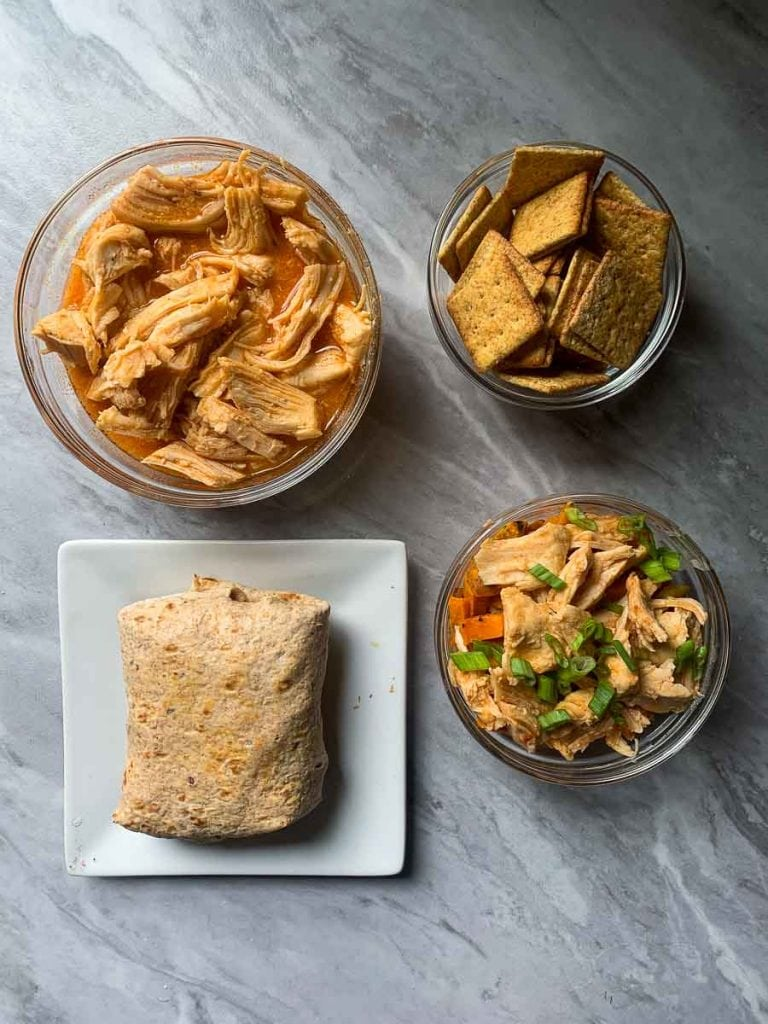 This is the healthy buffalo chicken made 4 ways. There is a bowl of the healthy buffalo chicken in the top left corner, a bowl of crackers next to it, a wrap, and chicken with sweet potatoes. These are all in a square.
