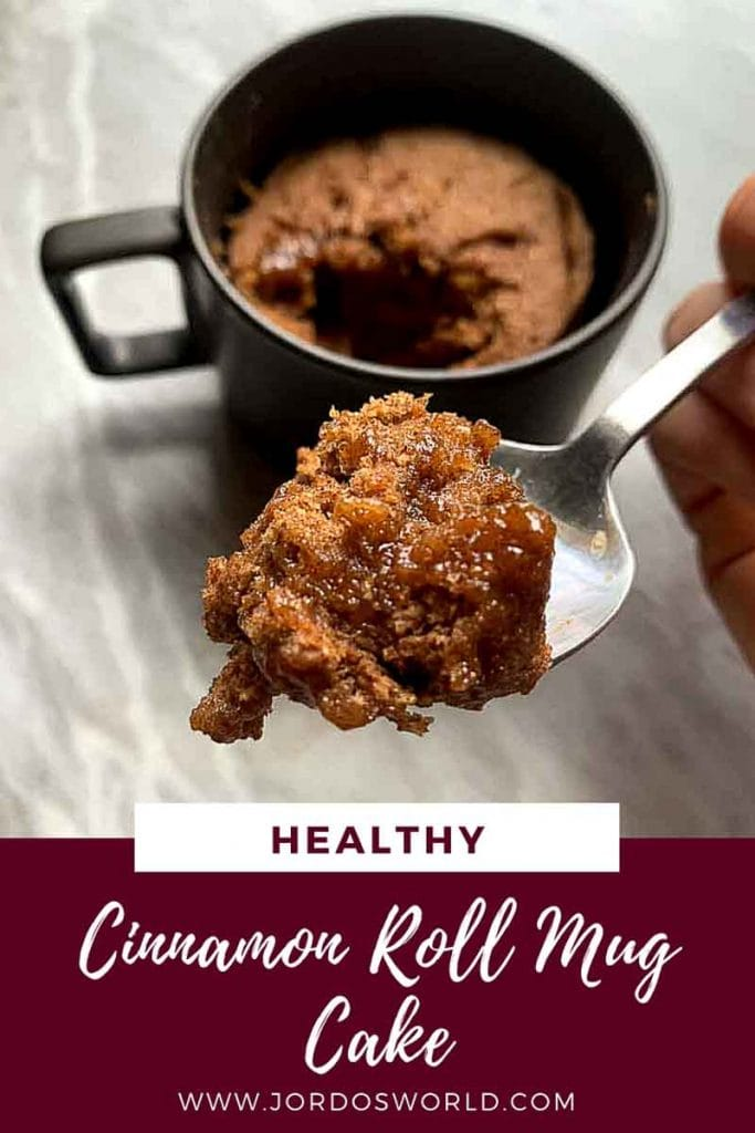 This is a pinterest pin for the healthy cinnamon roll mug cake. The mug cake is on a spoon and you can see the melted cinnamon and brown sugar. The title of the recipe is also on the post.