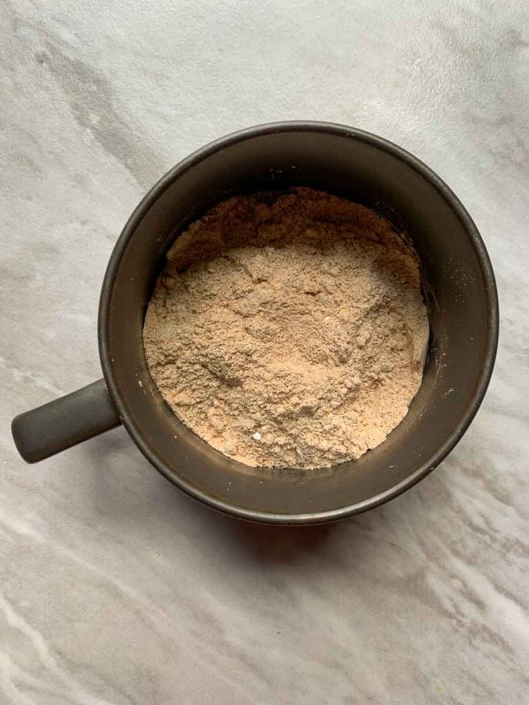 This is a mug with the dry ingredients for the cinnamon roll mug cake. It is dry white and brown ingredients mixed together.