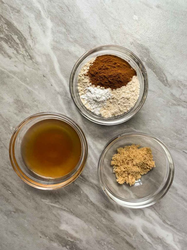 These are all of the ingredients for the cinnamon roll mug cake. There are 3 small bowls -- one with dry ingredients, one with wet ingredients, and one with brown sugar for the topping.