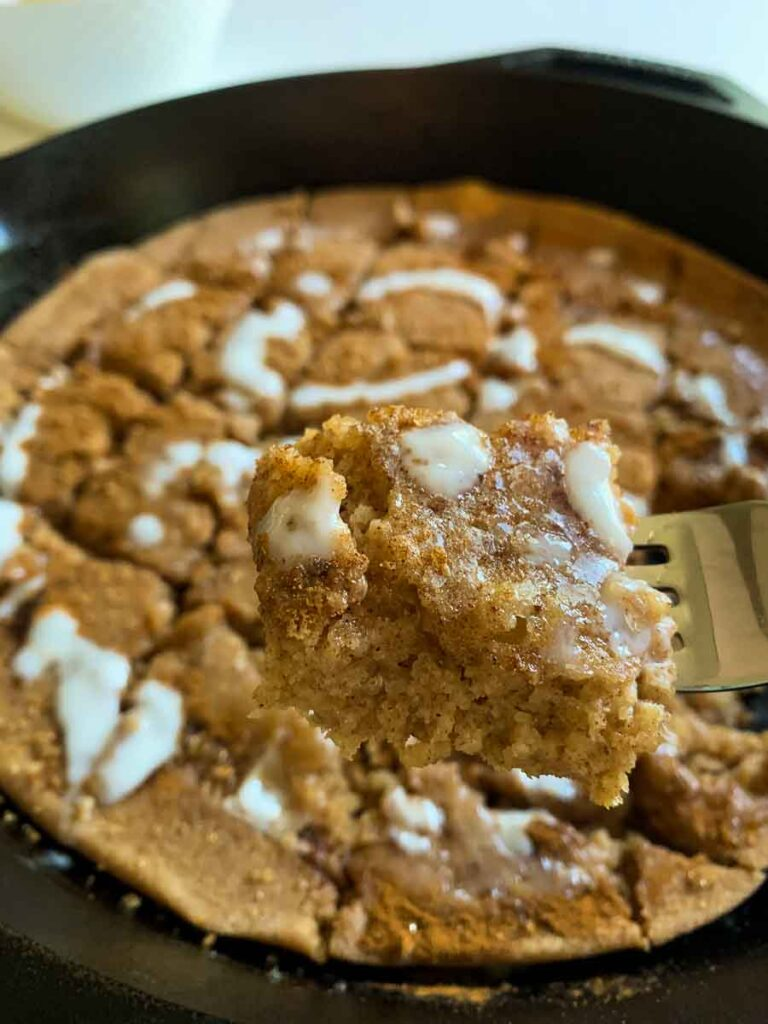 This is a picture of a cinnamon roll pancake skillet. There is a cast-iron skillet with a giant pancake in it. The pancake is topped with cinnamon, brown sugar, and a creamy white frosting. There is also a fork holding up a small piece of it.