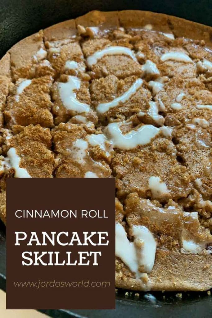 This is a pinterest pin for the cinnamon roll pancake skillet recipe. There is a cast-iron skillet with a giant pancake in it. The pancake is topped with cinnamon, brown sugar, and a creamy white frosting. The title of the recipe is also on the pin.