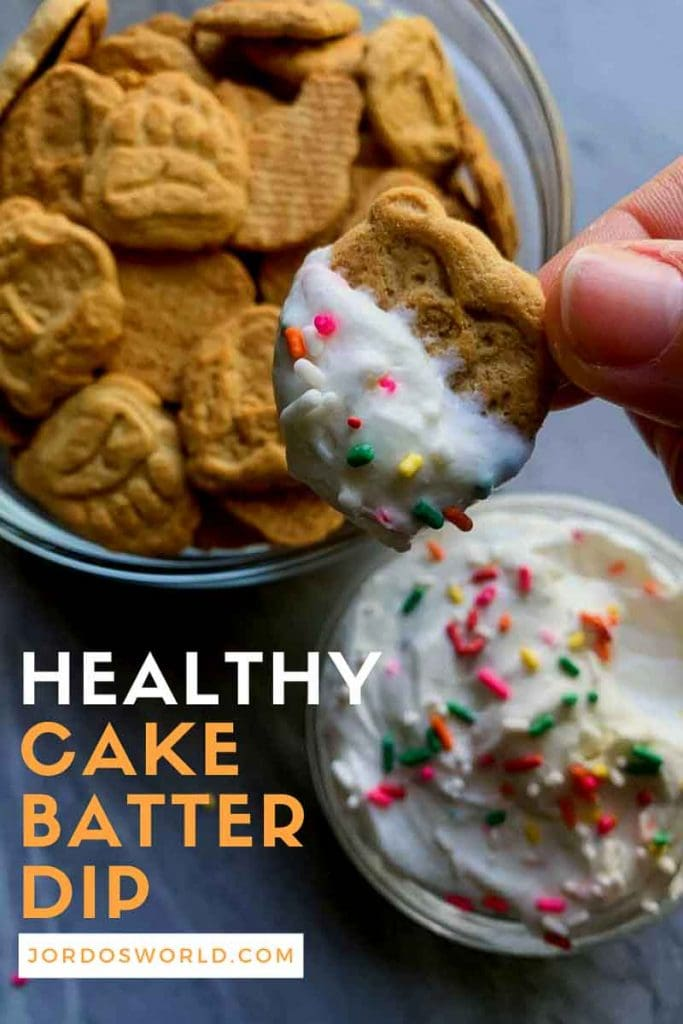 This is a pinterest pin for healthy cake batter dip. There is a clear glass bowl filled with white fluffy healthy cake batter dip, topped with funfetti sprinkles. The title of the recipe is on the picture as well. There is also a hand holding up a small bear bite with the dip on it.