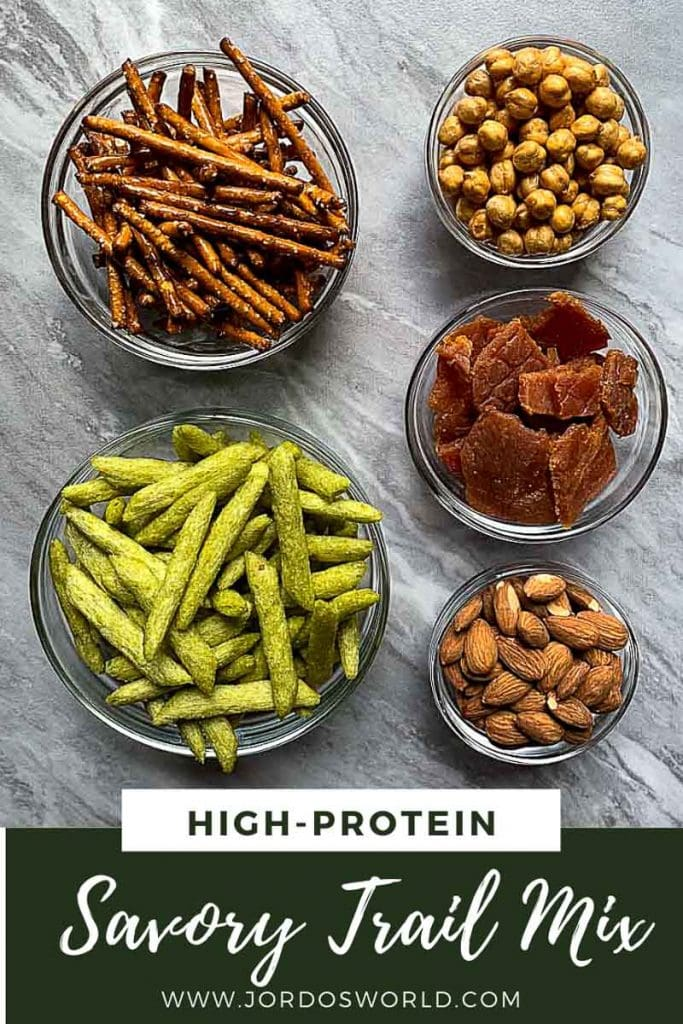 This is a pinterest pin for protein trail mix. There are glass bowls filled with each of the ingredients, which are pretzel sticks, baked snap peas, turkey jerky, crunchy chickpeas, and roasted almonds.