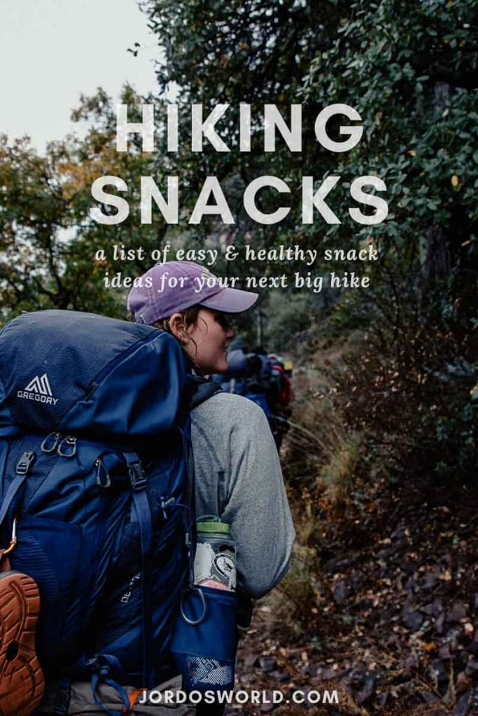 "This is a pinterest pin for the post about hiking snacks. There is a picture of a person with a big blue hiking backpack on hiking through the trees on the side of a mountain. The title of the post, ""Hiking Snacks"" is on the picture as well."
