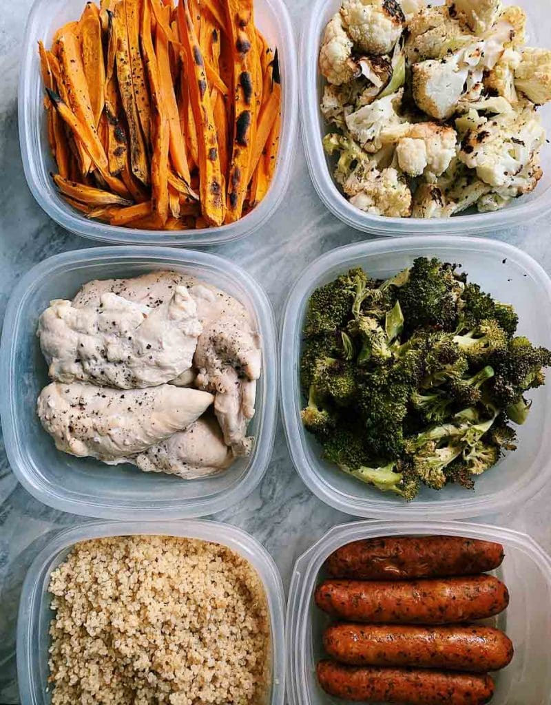 This is a picture of meal prep foods. There are multiple containers of varying prepped foods including vegetables, meats, and grains.