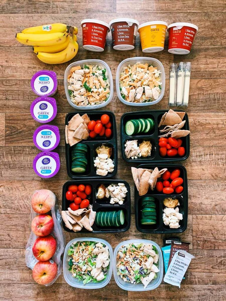 This is a completed meal prep with everything laid out for the week. There are the breakfasts on top (bananas and oatmeal cups), lunches in the middle (salads with yogurts), and then the dinners in the middle (pita, chicken, and veggies). There are also snacks (apples, cheese sticks, rxbars) on the sides.