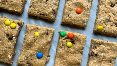 These are monster cookie protein bars. There are several rectangle bars mixed topped with mini colorful m&m's and mini chocolate chips.
