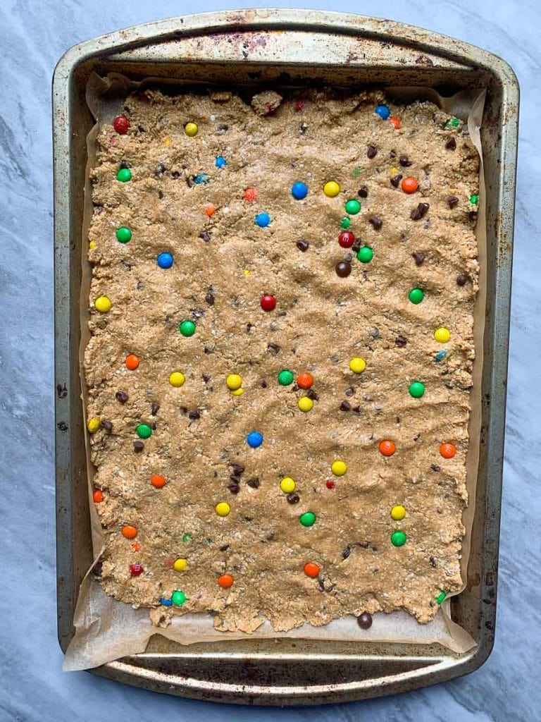 These are monster cookie protein bars. TThis is the dough smashed onto a baking sheet and it is topped with mini colorful m&m's and mini chocolate chips.