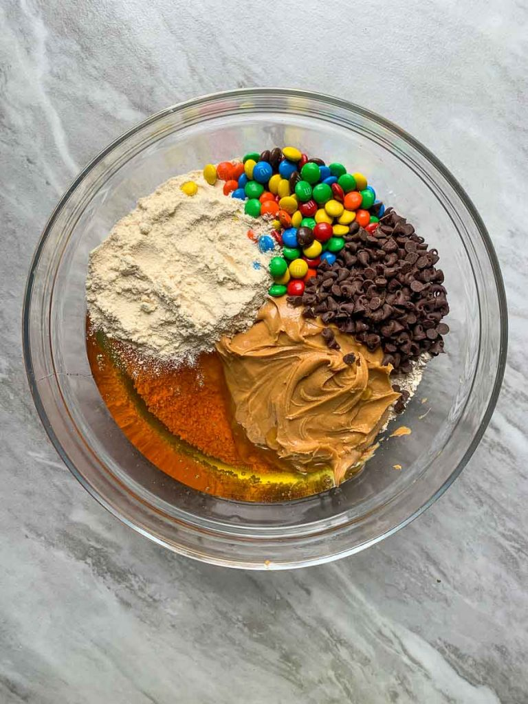This is a bowl with all of the ingredients for the monster cookie protein bars. There is honey, protein powder, peanut butter, chocolate chips, m&m's, and oat flour.