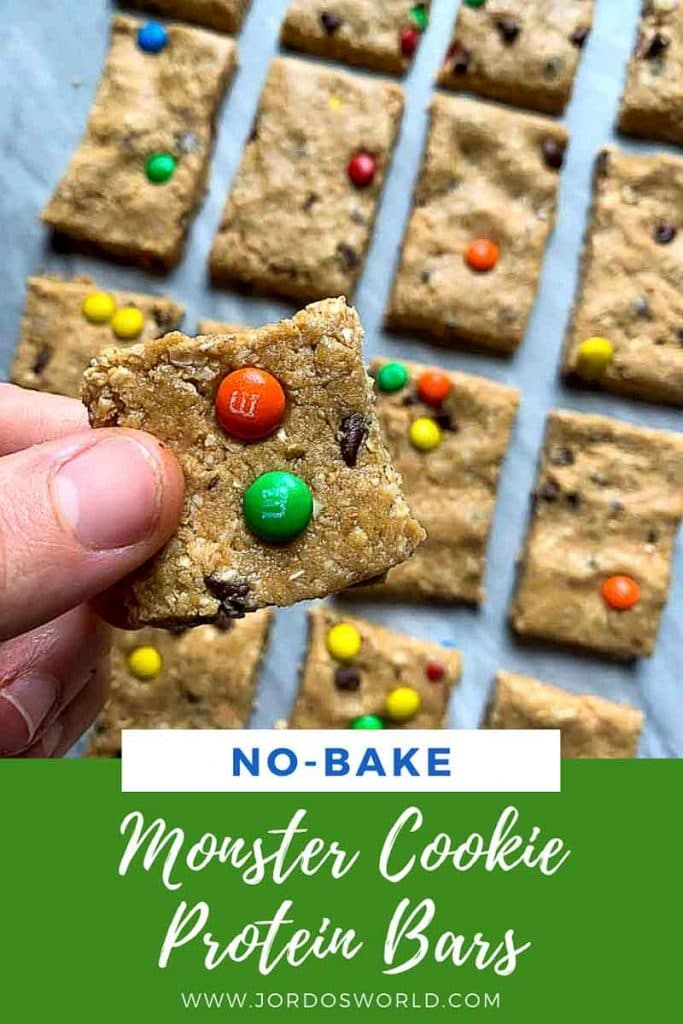This is a pinterest pin for monster cookie protein bars. There are several rectangle bars mixed topped with mini colorful m&m's and mini chocolate chips. A hand is holding up one of the protein bars. The title of the bars is also on the pin.