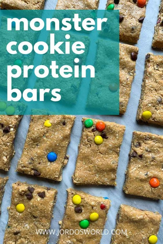This is a pinterest pin for monster cookie protein bars. There are several rectangle bars mixed topped with mini colorful m&m's and mini chocolate chips. The title of the bars is also on the pin.