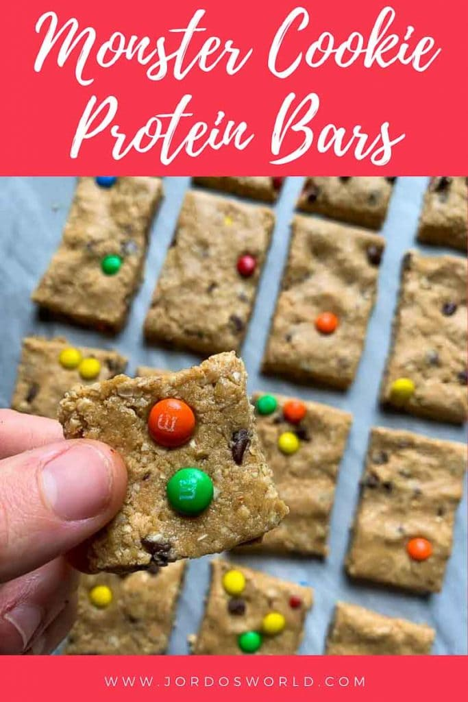 This is a pinterest pin for monster cookie protein bars. There are several rectangle bars mixed topped with mini colorful m&m's and mini chocolate chips. Two fingers are holding up one of the bars so you can see it up close. The title of the bars is also on the pin.