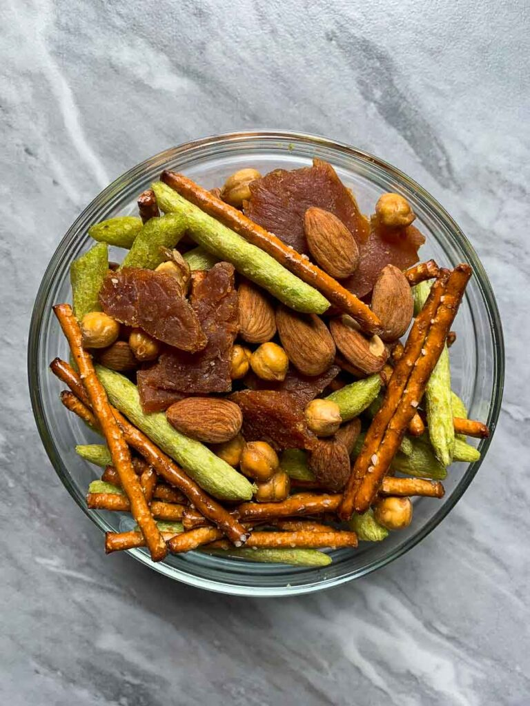 This is a bowl of protein trail mix. There is a glass bowl filled with pretzel sticks, baked snap peas, turkey jerky, crunchy chickpeas, and roasted almonds.