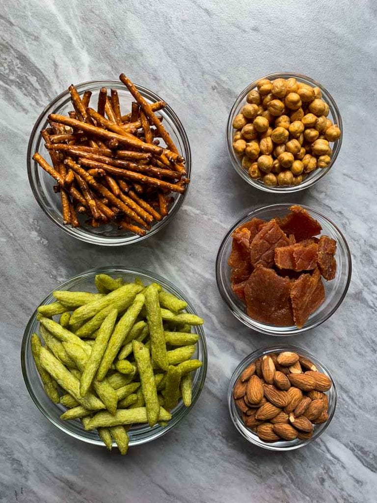 These are all of the ingredients for the protein trail mix. There are bowls with pretzel sticks, baked snap peas, turkey jerky, crunchy chickpeas, and roasted almonds.