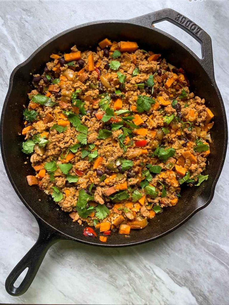 This is a cast-iron skillet with the burrito bowl in it. The burrito bowl is ground turkey, sweet potatoes, black beans, peppers, onions, and cilantro all mixed together.