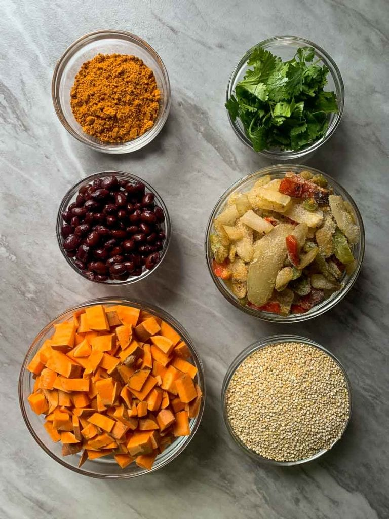 These are the ingredients for the burrito bowl meal prep recipe. There are sweet potatoes, black beans, taco seasoning, cilantro, peppers and onions, and quinoa.