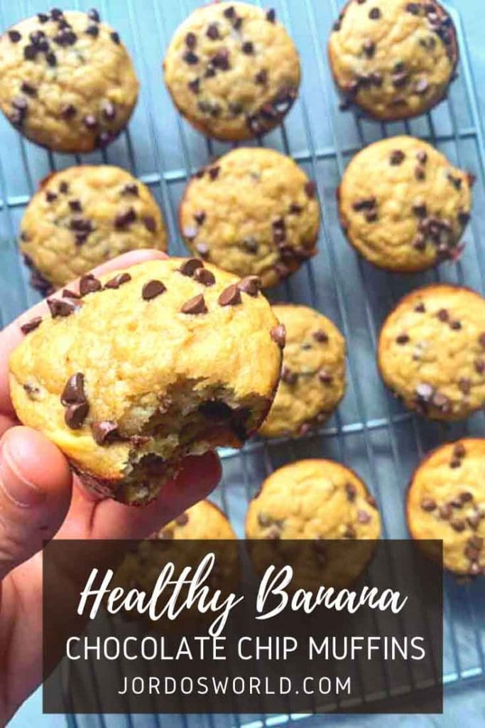 This is a pinterest pin for healthy banana chocolate chip muffins. There is a wire rack with circle muffins covered in mini chocolate chips. There is also a hand holding up a close-up version of one of the muffins.
