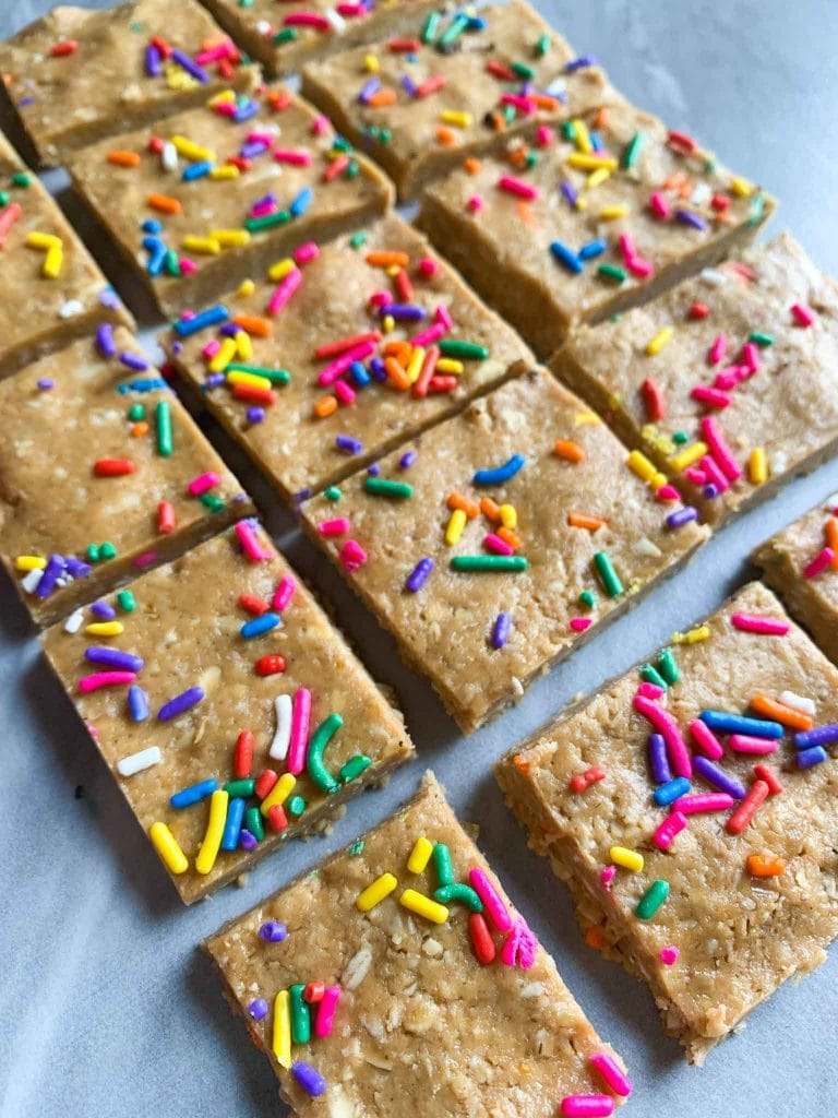 These are birthday cake protein bars. There are rows of cut protein bars in small squares. Each bar is topped with funfetti sprinkles.
