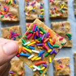 These are birthday cake protein bars. There are rows of cut protein bars in small squares. Each bar is topped with funfetti sprinkles. There is a hand holding up a protein bar topped with funfetti colorful sprinkles.