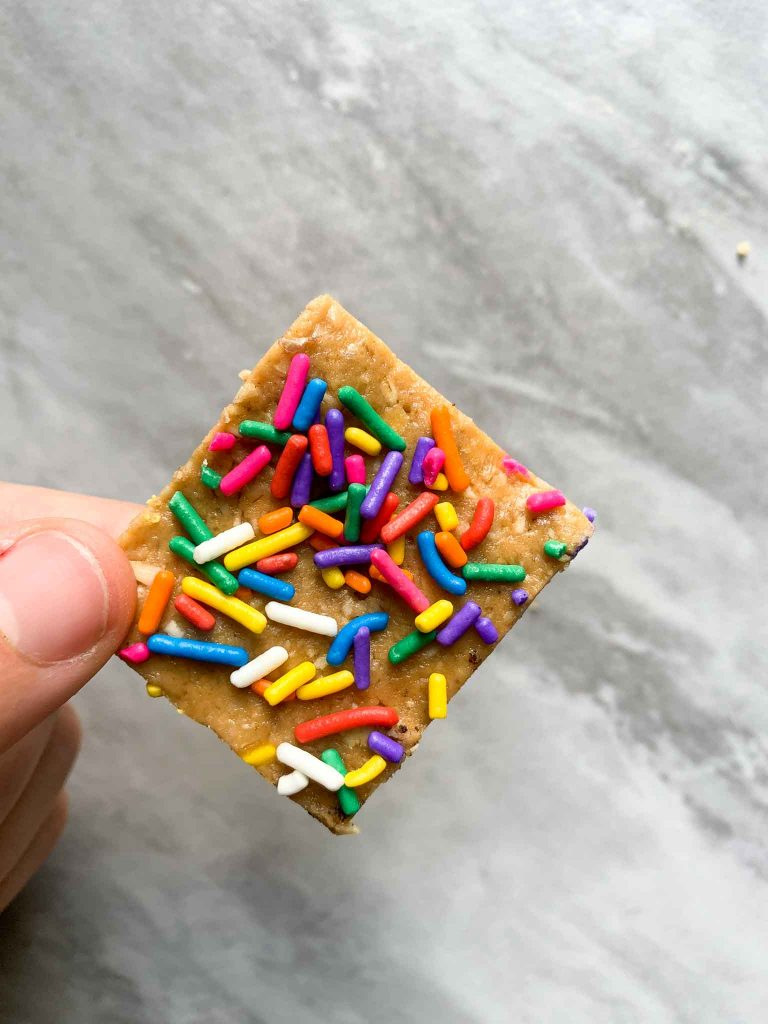 This is a piece of the birthday cake protein bars. There is a small square protein bar topped with colorful funfetti sprinkles.