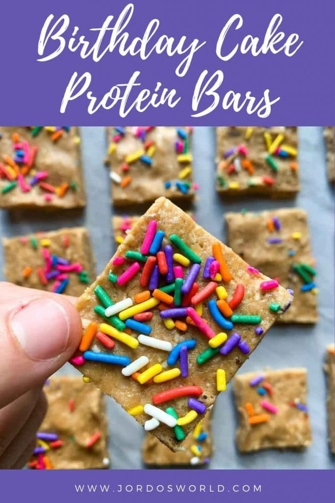 This is a pinterest pin for the birthday cake protein bars. There are small squares of protein bars topped with funfetti sprinkles. There is a hand holding up one of the bars as well.