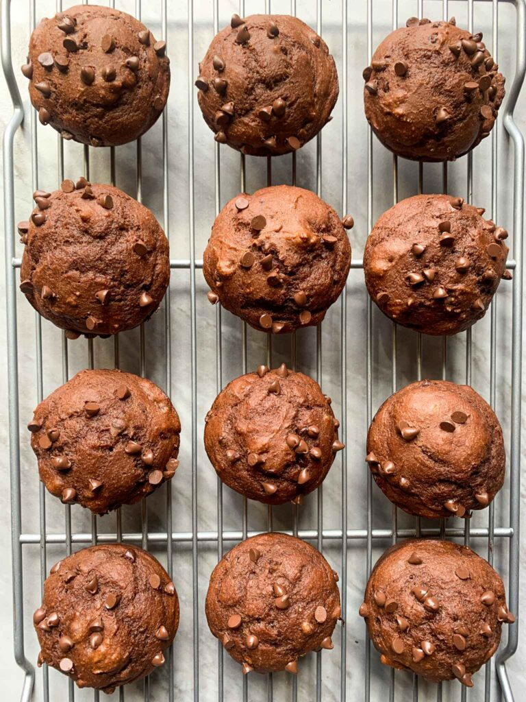 This is a picture of the chocolate banana muffins. There is a cooling rack filled with the double chocolate muffins, each brown and topped with mini chocolate chips.