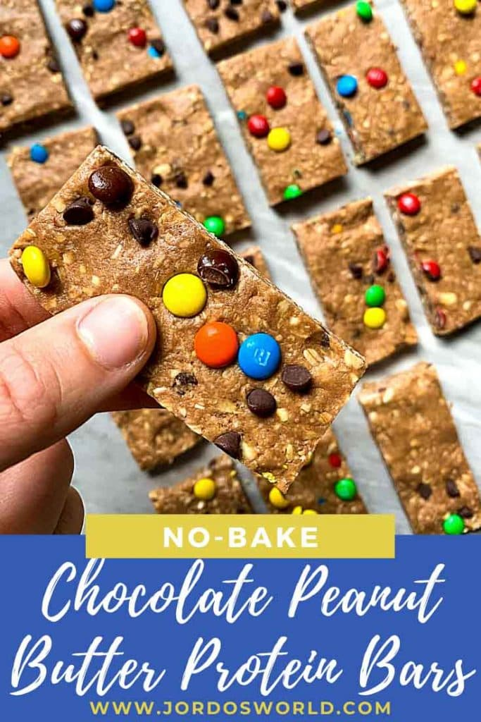 This is a pinterest pin for chocolate peanut butter protein bars. There is a pan filled with rectangle chocolate peanut butter bars topped with mini m&m's and mini chocolate chips. There is a hand holding up one of the bars as well.