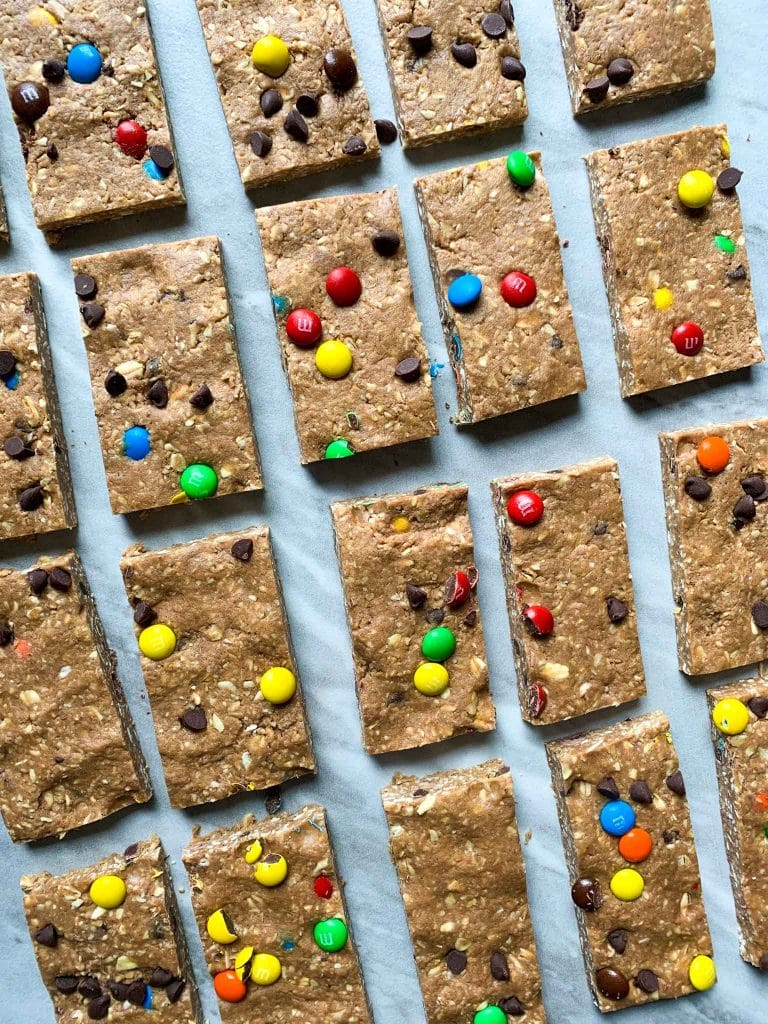 These are the chocolate peanut butter protein bars cut into pieces and on a baking sheet. Each bar is chocolate covered and topped with mini M&M's and chocolate chips.