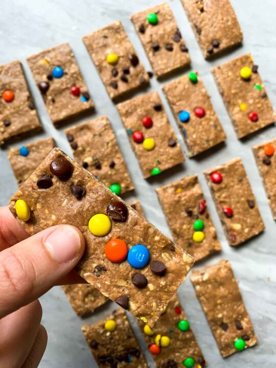 These are the chocolate peanut butter protein bars cut into pieces and on a baking sheet. Each bar is chocolate covered and topped with mini M&M's and chocolate chips. There is a a hand holding up one of the bars.