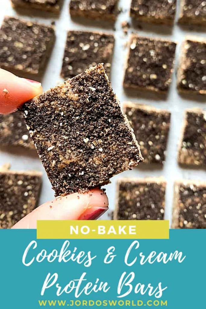 This is a pinterest pin for cookies and cream protein bars. There are rows of bars that are cut into squares and covered in crushed oreo dust. There is also a hand holding up one of the protein bars.