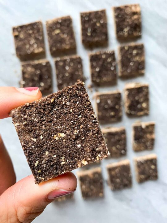 These are cookies and cream protein bars. There are rows of squares of protein bars. The bars are brown and each bar is topped with a dusted coating of oreos. There is also a hand holding one of the bars.