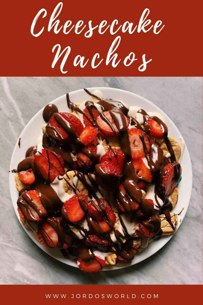 This is a pinterst pin for dessert nachos. There is a plate full of bear bites and topped with a cheesecake mixture, sliced strawberries, and drizzled chocolate.