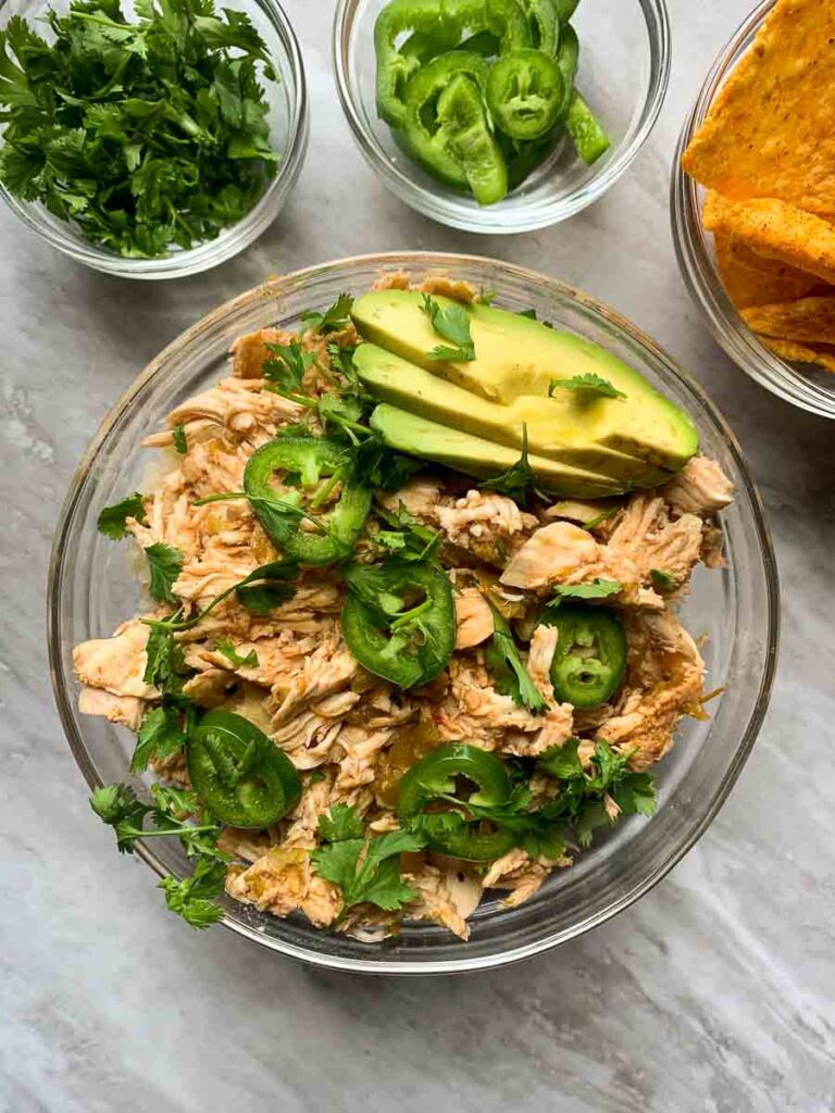 This is the final product for green chili chicken. There is a large glass bowl filled with shredded chicken and topped with sliced jalapenos, cilantro, and sliced avocado. There are small bowls filled with cilantro, jalapenos, and tortilla chips as well.