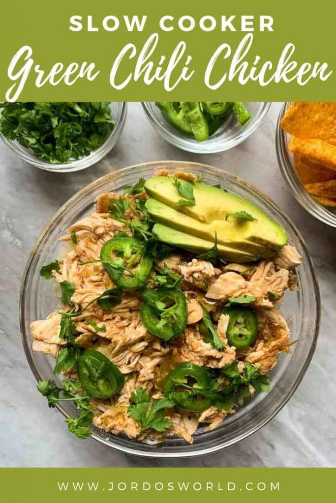 This is a pinterest pin for green chili chicken. There is a bowl filled with shredded chicken and topped with avocado, jalapenos, and cilantro. There are small bowls of these ingrdients and tortilla chips as well.