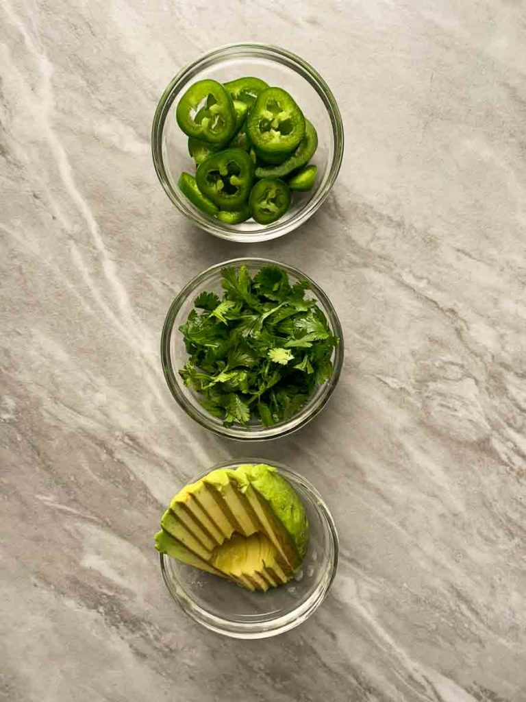 These are some additional topping ideas for the green chili chicken. There is a bowl with sliced jalapenos, chopped cilantro, and sliced avocado.