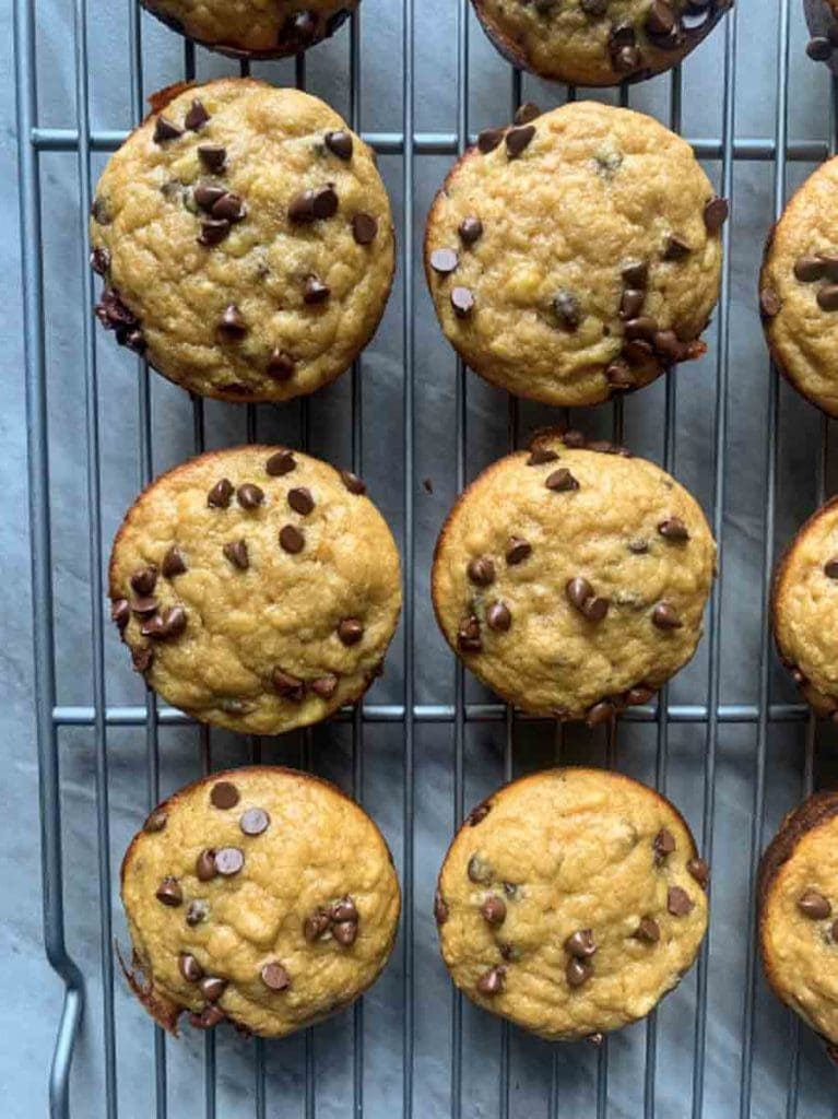 These are healthy banana chocolate chip muffins. The is a wire cooling rack filled with golden muffins topped with several melted mini chocolate chips. In this picture, the camera is zoomed in to 6 of the muffins.